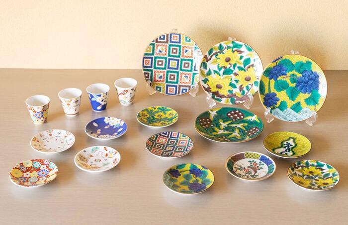 こちらも能美市にある九谷焼の窯元、「青郊窯(せいこうがま)」のおしゃれな食器セットです。左側のカップと豆皿が「吉祥」シリーズ、右側の5号皿と豆皿が「古九谷 名品コレクション」になります。どちらの食器セットも、日本の伝統文様を取り入れた美しい色絵が魅力的です。