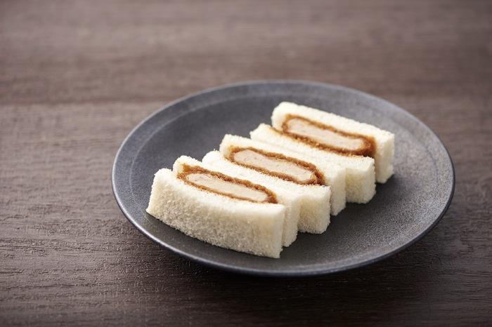 """「まい泉」の""""ヒレかつサンド""""は、一つ一つの素材にこだわったサンドイッチ。やわらかいヒレかつと弾力のあるパン、甘めのソースが合わさり口の中いっぱいに美味しさが広がります。"""