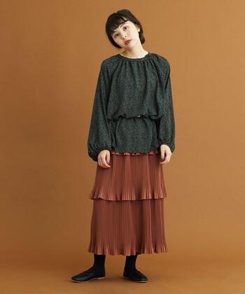 プリーツから生まれる独特な陰影が上品なブラウンのスカートに、柄のダークトーンのトップスを合わせて、上級者のコーデ。ティアードスカートのようなボリューム感のあるスカートにはウエストマークでメリハリをつけると、脚長効果が期待できますよ。カラーだけでなく、お洋服の質感でも秋らしさを感じるコーデです。