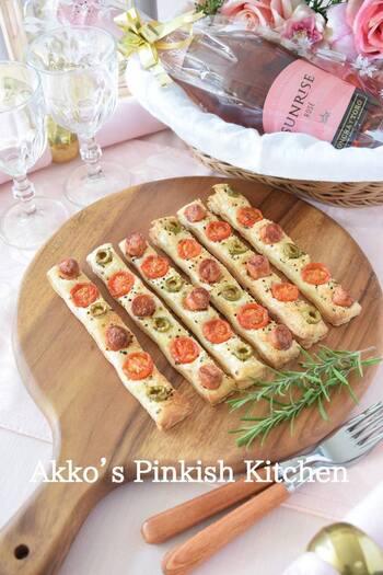 冷凍パイシートにウインナー、ミニトマト、オリーブをのせたピザ風のパーティースティック。具材が落ちないよう押すように乗せるのがポイントです。