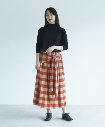 ぱっと目を引くオレンジのスカートには、ブラックのアイテムのみでコーデを引き締め。そうすることで子どもっぽさはどこへやら。旬な着こなしにたちまち変身!