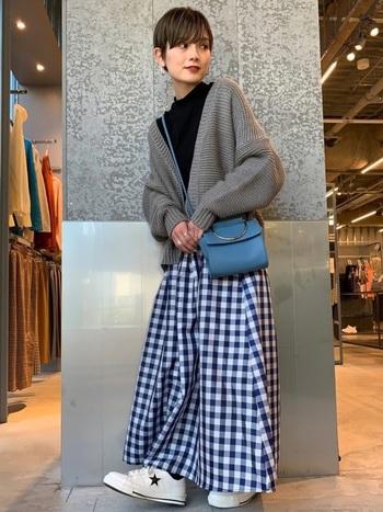 マキシ丈のギンガムチェックスカートは、ざっくり編みのカーデで大人仕様に。暗くなりがちな秋冬はバッグで綺麗めなさし色を取り入れて♪