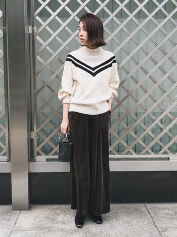 大胆なVラインデザインのハイネックニットに、スカートのようなフレアシルエットのベロアパンツをコーディネート。足元は黒のパンプスで、大人っぽくまとめています。