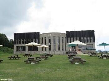 ピクニックテーブルとベンチのある『芝生広場』。背景は『レストランスカイアーク』。