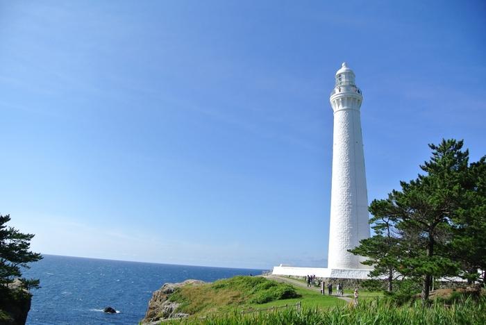 """このような、まっしろな灯台がお目見え。  空と海の""""ブルー""""とのコントラストが織り成す景色は、まさにまさしく絵になる美しさです。  実は、なんと日本一の高さ!遠くから見たら分かりづらいですが、実際近くに行ってみると、首が痛くなるほど、ずーっと見上げてしまうくらい、迫力があります。  また、周辺を飛びまわる白っぽい鳥も見受けられるはず。実は近くにはウミネコの繁殖地となっている小さな島「経島(ふみしま)」があるんです。ウミネコの鳴き声もまた、この場所ならではの思い出になります。"""