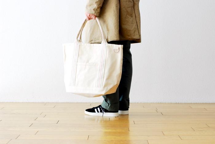 手に持つ部分は生地を折って馴染むように作られています。大きめだから、毎日持ち歩くものを何でも入れて持ち運べる。外ポケットの他に、内側にも小さなポケットが付いています。