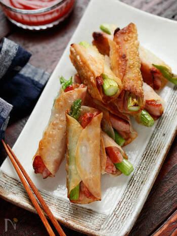 餃子の皮でウインナーとアスパラをくるっと巻けば、簡単で美味しいおつまみに。巻き終わり部分から焼くときれいに仕上がりますよ。
