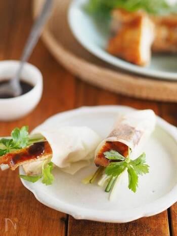 鶏肉を使えば、おうちでも北京ダック風が作れます。パリッと焼いた鶏肉、長葱、キュウリ、パクチーを、特製だれと一緒に春巻きの皮で巻けば完成。食べ応えも満点です。