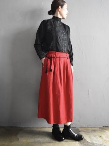 黒のレースブラウスを、赤のロングスカートにタックインした着こなし。ウエストに細い紐ベルトを合わせて、トレンド感をアップしています。足元も黒で合わせて、レデイライクなコーディネートに。