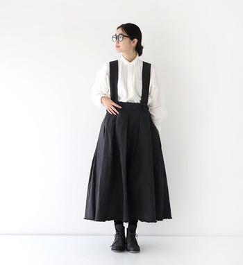 白の長袖ブラウスを、黒のジャンパースカートに合わせたスタイリングです。足元も黒でまとめて、大人ガーリーなモノトーンコーデに仕上げています。
