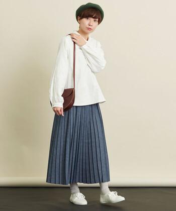 白のゆったり長袖ブラウスに、ネイビーのプリーツスカートを合わせた着こなし。あえてタックインしないスタイリングで、大人っぽさをアピールしています。足元を白でまとめて、統一感のあるコーディネートに。
