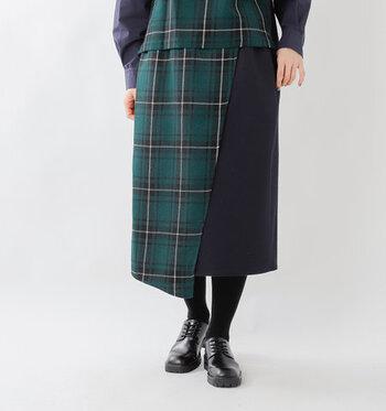 季節感たっぷりな、ウール素材を使用したチェック柄のスカートです。無地のネイビースカートの上に、チェック柄の布を巻き付けたような、ラップスカート風のデザインが特徴。総チェック柄はコーデが難しそうと感じる人にも、おすすめのアイテムです。