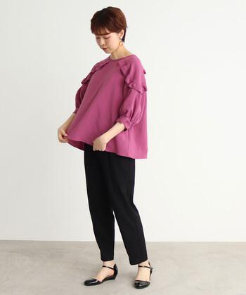 肩に大胆なフリルデザインをあしらった、ピンクのふんわりブラウス。甘めな印象のアイテムなので、パンツとシューズを黒で揃えてガーリーになり過ぎないコーディネートにまとめています。