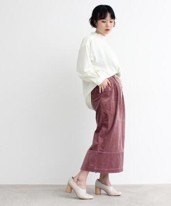 季節感たっぷりなコーデュロイ素材のピンクスカートに、白のゆったりトップスを合わせたコーディネートです。トップスはフロントだけをタックインして、タイトスカートとのバランス感をしっかりアピール。シューズも白系で揃えて、清楚な雰囲気で着こなしています。