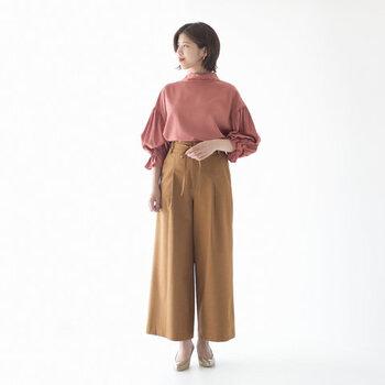スタンドカラーとバルーン袖で、トレンド感たっぷりなローズピンクのブラウスです。キャメルのワイドパンツにタックインしてから、程よくたるませているのがポイント。ナチュラルな大人っぽさのアピールに繋がります。