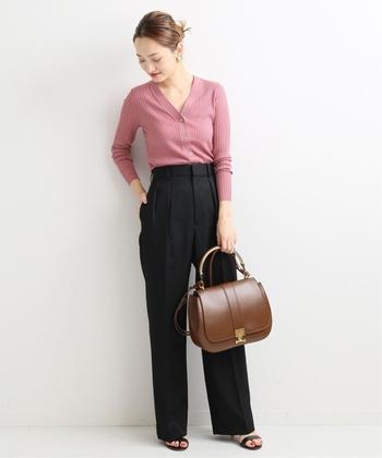 ピンクのVネックカーディガンは、ボタンを留めてパンツにタックインすることでトップス風の着こなしに。程よい胸元の開きと黒のパンツで、オフィススタイルにもOKなベーシックコーデの完成です。