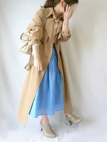 ベージュのロング丈トレンチコートに、ブルーのスカートを合わせた上品なコーディネートです。シャツと小物もベージュでカラーを揃えて、ブルーのスカートを主役にした着映えスタイルの完成です。