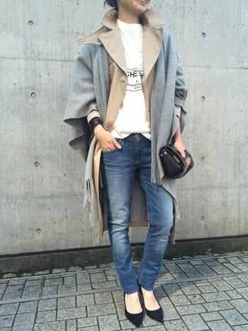ベージュのトレンチコートの上から、大判のグレーストールを羽織った着こなしです。Tシャツとデニムのプレーンなコーディネートも、ストール一枚で季節感がアップ。寒い時期にはもう少し大きいストールや、厚手のアイテムを選ぶと防寒性も◎です。