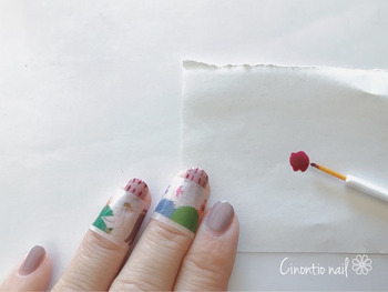 最初に、スモーキーカシミヤを2度塗りしてベースを作り、爪の半分にマスキングテープを貼ったあと、細筆でボルドーの縦ラインを引きます。次に「+」の形になるようにボルドーで横ラインを。