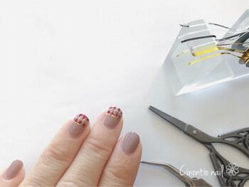 同じくゴールドも「+」の形になるようにラインを引き、マスキングテープを剥がしたら、ゴールドのラインテープを爪の中央に貼り、全ての爪にトップコートを塗ったら完成です。