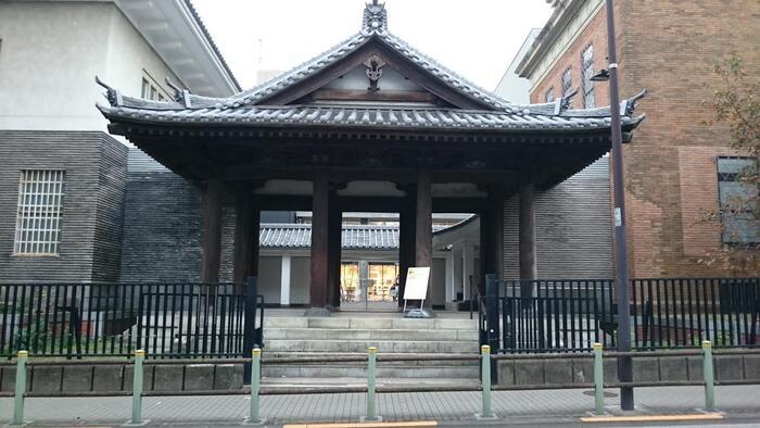 """無料で利用できる、もう一つのお勧めのスポットが、東京藝大美術学部構内にある「geidai art plaza」です。 【大正2(1913)年建築の「東京藝術大学旧東京美術学校玄関(通称:黒門)」。正面突き当りが""""geidai art plaza""""。黒門は、東博から見て藝大正門の手前並び。】"""