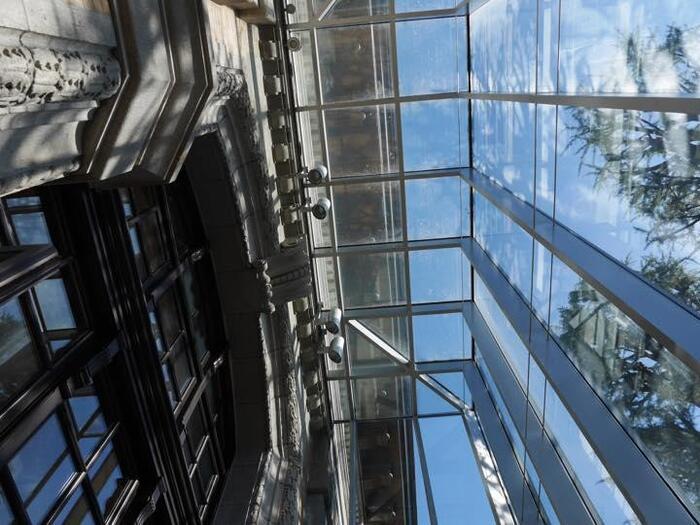 当図書館の見所は、ずばり建築です。 明治期、昭和、現代の建築が融合した建物。そして建物と外部が繋がれることによって生まれる静謐な空間です。  子ども図書館は、二つの建物からなりますが、本館の「レンガ棟」は、明治39年に建てられたルネッサンス様式の洋風建築で、昭和4年に増築、平成に改修した三つの時代の建築が一体となった建物です。  新館の「アーチ棟」は、平成27年に竣工した前面ガラス張りの美しい曲線を描いた建物。「レンガ棟」の改修と「アーチ棟」の設計は、世界的建築家・安藤忠雄です。【明治期の外壁をガラス壁で改修した「レンガ棟」の外壁】