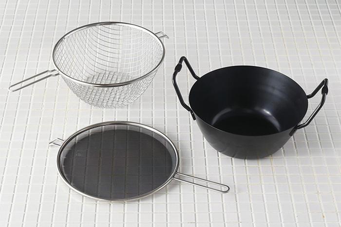 料理研究家の有元葉子さんが提案する「la base(ラバーゼ)」の「鉄揚げ鍋セット」は、揚げ物にあると嬉しい道具がセットになった、嬉しいアイテム。  錆びにくく、耐久性に優れたブルーテンパー加工を施した鉄鍋と、その中にちょうど収まる大きさの両手付き揚げかご、さらには油はねを防ぐネットの3点がセットになっています。