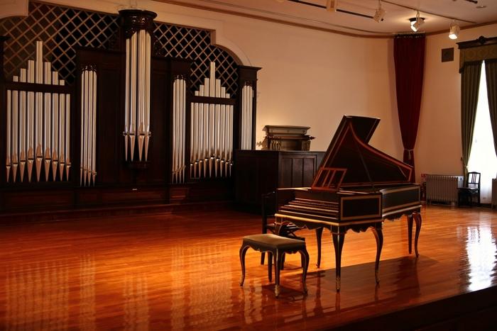 """【日本における音楽教育の中心的な役割を担ってきた「旧東京音楽学校奏楽堂」は、""""生きた文化財""""として、建物の公開のみならず、貴重な音楽資料を展示する他、定期的に演奏会が行われている。  東京藝大音楽部学生、院生が演奏する「日曜コンサート」は、通常の入館料のみで入場できる。他にも特別コンサートが様々に開催される(入場料はコンサート毎に異なる)。「奏楽堂」の基本の公開日は、日・火・水曜日だが、月曜日以外は、ホールの使用がなければ公開。公開日、コンサート等などの詳細は、HPで確認のこと。  (画像は「奏楽堂」内ホール舞台。舞台正面のパイプオルガンは、コンサート用としては、日本最古。大正9(1920)年に徳川頼貞侯が英国より購入、昭和3年(1928)に東京音楽学校へ寄贈したものだが、現役であり、演奏でその音色を聴くことが出来る。)】"""
