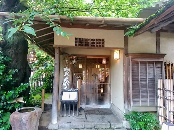 「喫茶去」は、創業140年を誇る、老舗料亭「韻松亭」が営む喫茶室。 情趣溢れる外観同様に、店内もしっとりとした茶室風の設えで、ガラス張りの開放感ある窓には、上野の杜らしい景色が広がって、落ち着いた一時を楽しめます。  【「五條天神社」と「花園稲荷神社」」の石鳥居のすぐ脇にある「喫茶去」の入り口。喫茶去の右側が「上野の杜 韻松亭」となっている。】