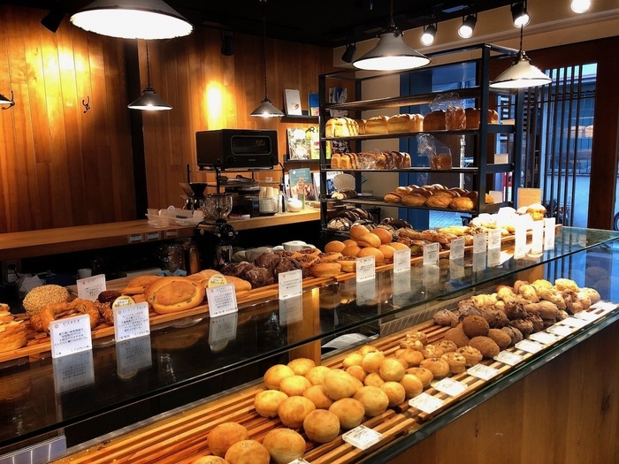 木のぬくもり溢れるおしゃれな店内には、食パンやクロワッサンをはじめ、約50種類以上もの様々な種類のパンが並びます。どれもここでしか味わえない、オリジナリティあふれる美味しいパンばかり。店内にはカフェも併設されており、イートインスペースでモーニングやランチなどのフードメニューもいただくことができます。