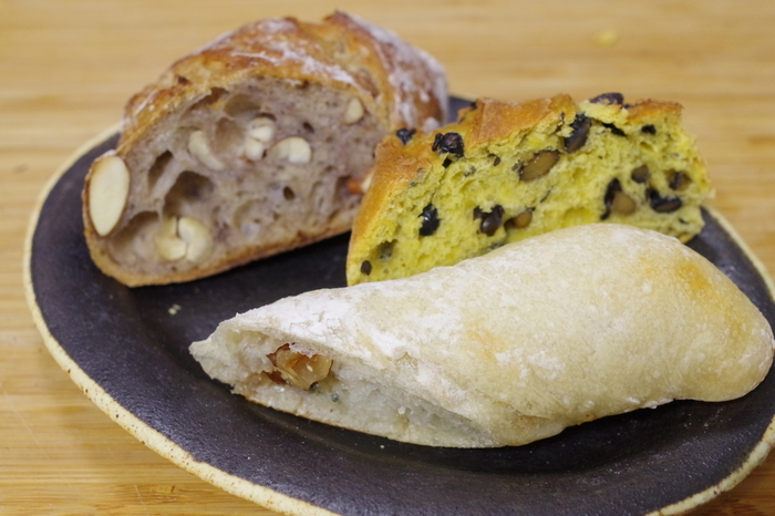 ナッツ好きの方には、チーズとクルミの風味を楽しめる「ゴルゴンゾーラ」(写真手前)や、アーモンドやカシューナッツが入った「ナッツ・トゥ・ユー」(写真奥)もおすすめです。お店の中と外にはテーブル席があり、コーヒーや紅茶とともに美味しいパンをイートインできます。