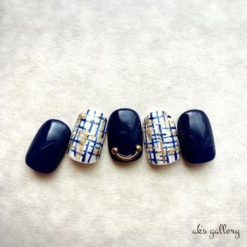 白ベースにブルーとゴールドを描いた爽やかなツイード柄に、深い青色ネイルと組み合わせて。中指のゴールドのパーツが上品で、マリン風に変身します。