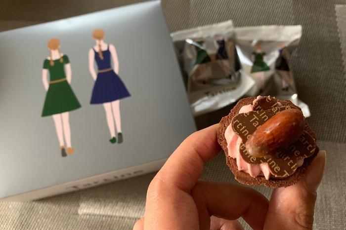 一口サイズがかわいい「Wストロベリーチョコタルト」。シルバーグレーの箱に、緑と紺のワンピースを着たタルティン姉妹の後姿が描かれています。よく見ると、靴や髪型も微妙に違っていています。