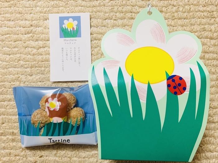 「マルチェナ」は、タルティン家に咲くお花をコンセプトに作られたパイのお菓子。真ん中にはホワイトチョコレートが添えてあり、サクッと軽い食感が楽しめます。小袋を見ると、女の子の髪飾りにもなっているのがキュート!