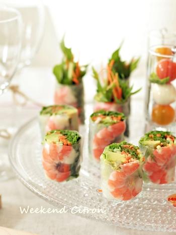 ライスペーパーに、エビ、アボカド、水菜などを巻いた生春巻き。大葉の代わりに、パクチーやバジルなどを巻いても◎海老を奥に置いて野菜をはみ出すようにして巻くのもコツです。ガラスのプレートに立てるように盛り付けると見栄えもアップ!