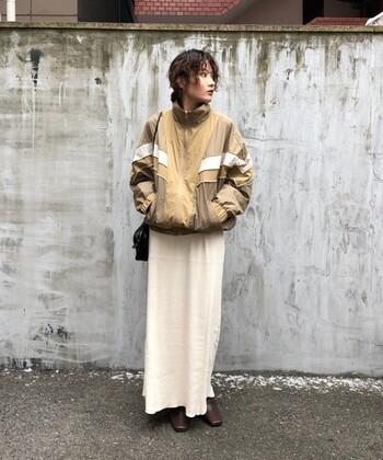 くすみカラーのナイロンジャケットに、白のロングスカートを効果的に取り入れたスタイリング。足元に茶色のシューズを合わせて、白が浮きすぎないようにナチュラルに馴染ませています。