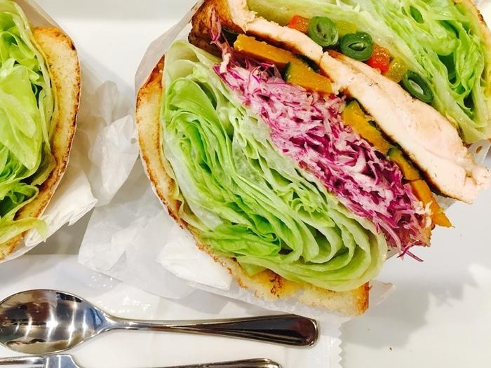 野菜がこれでもかというほど挟んだサンドイッチはインパクト大!萌え断面として大人気のボリューム三度は、思わず写真を撮りたくなってしまうほど。バジルチキンサラダには、レタス、かぼちゃ、パプリカ、レッドキャベツ、いんげん、パプリカ、バジル、マリネチキンが入っています。大きな口を開けてがぶりといただきましょう!