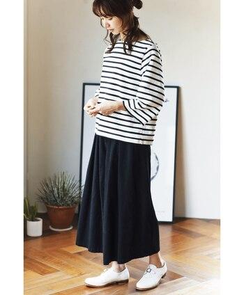 白黒のゆったりボーダートップスに、ネイビーのフレアスカートを合わせたリラックスコーデ。足元は白のシューズで、爽やかな印象にまとめています。おうちで過ごす休日や、来客のある日などにもぴったりな着こなしですね。