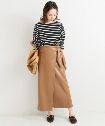 ゆったりシルエットの白黒ボーダートップスを、キャメルのレザーラップスカートにタックインした着こなしです。秋冬らしさがアップするレザー素材を合わせるだけで、定番ボーダーコーデがこなれ感たっぷりに仕上がります。