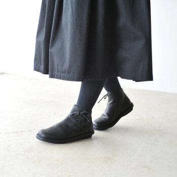 取り外しが可能なソールとインソールで構成された、黒のショートブーツ。細やかなお手入れが可能で、ゆとりのある履き心地も魅力の一足です。シューレースで足首まわりのサイズ感を調節できるため、冬用の厚手ソックスを履いても窮屈さを感じにくくなっています。