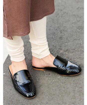 編み込みデザインがスタイリッシュな印象を与える、黒のエナメルスリッパサンダルです。サッと履けて歩きやすく、どんなコーディネートにも馴染む使い勝手抜群のシューズ。フェミニンにもカジュアルにも、大活躍してくれます。