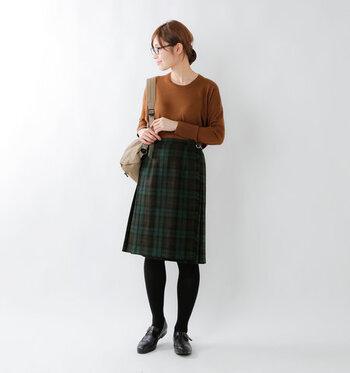 グリーン×ブラウンがベースの、秋冬カラーを取り入れたチェック柄台形スカート。ブラウンのトップスをタックインして、タイツとローファーでスクールガール風に着こなしています。ジャケットやアウターなど、どんなアイテムを合わせてもOKのベーシックなスタイリングです。