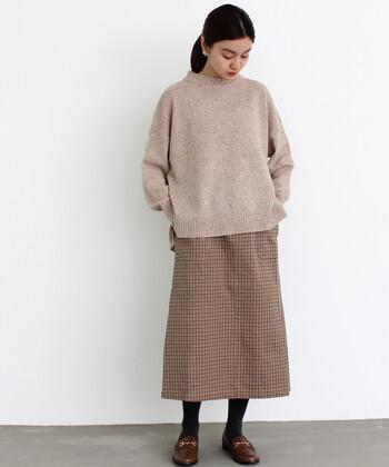 ロング丈のチェック柄台形スカートに、色味を合わせたハイネックニットを合わせた着こなしです。足元のローファーも色味を揃えて、秋冬コーデにぴったりな統一感のあるカラーリングでまとめています。