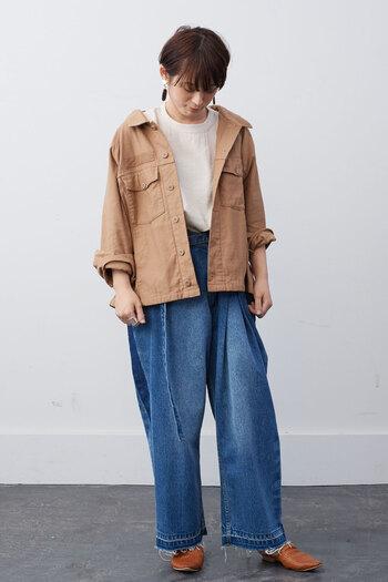 キャメルカラーのオーバーシャツジャケットに、デニムのワイドパンツを合わせたコーディネート。シンプルなトップスを合わせたメンズライクな着こなしに、大ぶりなピアスで女性らしさをさりげなくプラスしています。袖をラフにまくって手首を見せるのも、フェミニン度アップのポイントです。