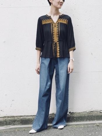 黒×マスタードカラーの刺繍ブラウスとワイドデニムの大人ボヘミアンスタイル。長めのブーツカットの裾から覗く白のポインテッドトゥのフラットシューズが、全体に明るさを加え、重さを軽減しています。