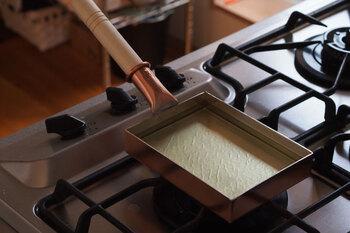 玉子焼鍋の7分目くらいまで油を注いだら、弱火~中火でおよそ5分、油の表面がゆらゆらと揺れ、少しだけ泡が出るくらいまで煮ます。ただし内側の錫は高温になると溶け出してしまうので、火加減には気をつけて下さい。