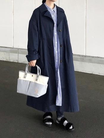 ネイビーのゆったりサイズのトレンチ。ブルーのストライプワンピに、同じくブルー系のバッグをセレクトして全身に統一感を出します。