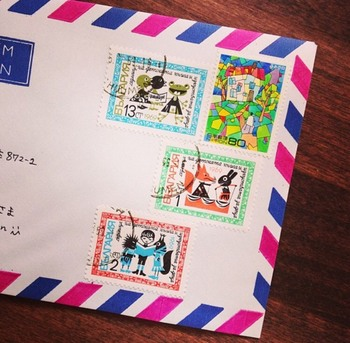 ちなみに、シンプルに洗練された雰囲気をプラスしたいなら、海外の切手を組み合わせるのもいいアイディアです。  もちろん、国内の郵便物には郵便料金としてカウントされませんので、「使用済みの海外切手」でOKですよ。  色味やテイストを揃えて、記念切手(写真右上)と海外の切手を一緒に貼り付ければ、まるでエアメールのようなオシャレな佇まいに。
