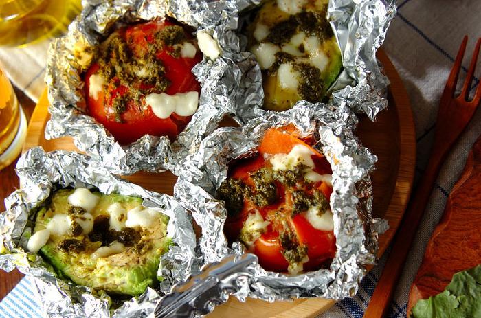 トマトもアボカドもまるまる使った豪快アウトドアレシピ。モッツァレラチーズとバジルソースがおいしさのポイントです。
