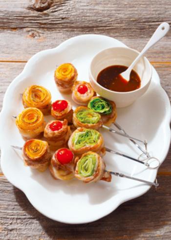 プチトマト、レタス、ズッキーニを豚バラ薄切り肉でくるくると巻いた串刺しレシピです。オレンジ・赤・みどりなど、カラフル野菜をチョイスして。
